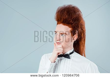 Stylish redheaded young man with bouffant on head. Thoughtful boy wearing shirt with bow-tie poster