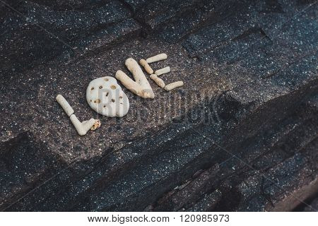 Word Love made of shells collected on a granite stone