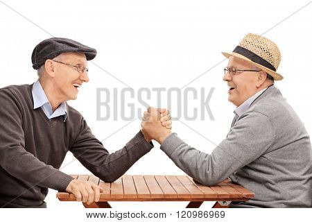 Two senior man having an arm wrestle competition seated at a table isolated on white background