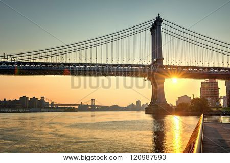 Gorgeous fiery orange sunset with a sunburst behind Brooklyn Bridge, New York, viewed across the water of the East River from a pier