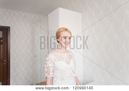Gorgeous bride with wedding bouquet makeup and hairstyle in bridal dress at home waiting for groom.