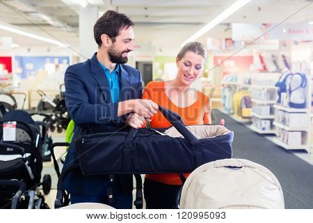 Couple in baby shop buying stroller, the woman in pregnant