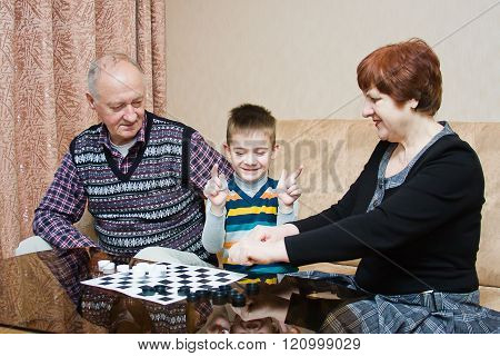 A Grandmother, Grand-dad, Play With A Grandchild In Checkers