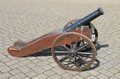 A Vintage Naval Cannon on Large Wooden Wheels. poster