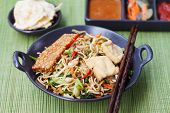 Mi goreng, mee goreng Indonesian cuisine, spicy stir fried noodles with tempeh and assortment of asian sauces poster