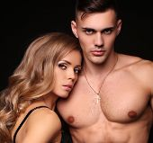 fashion studio photo of beautiful couple with sportive sexy bodies gorgeous woman with long blond hair embracing handsome brunette man poster