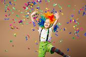 Little boy in clown wig jumping and having fun celebrating birthday. Portrait of a child throws up a multi-colored tinsel and confetti. Birthday boy. Positive emotions. poster