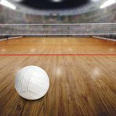 Sports arena full of fans in the stands with volleyball on wood flooring court. Deliberate focus on ball and shallow depth of field on background net and court. Floodlights flare for effect and copy space. poster