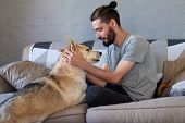 hipster man petting and rubbing his dog, loving affection relationship bond between owner and pet poster