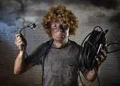 young man with funny curly wig holding electrical cable smoking after domestic accident with dirty burnt face and shock electrocuted expression in electricity DIY repairs danger concept in black smoke background poster