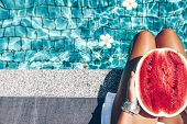 Girl holding watermelon in the blue pool, slim legs, instagram style. Tropical fruit diet. Summer holiday idyllic. poster