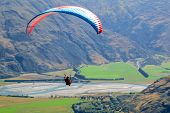 Paragliding sportsman flying high over mountains with a parachute wind break, gliding over fields with the wind poster