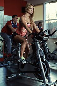 Group of young sporty people at spinning class. Fitness team doing bicycle exercise in the gym. Sport, lifestyle and healthcare concept. ** Note: Visible grain at 100%, best at smaller sizes