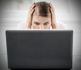 Stressed frustrated businesswoman sitting behind notebook touching her head in frustration.