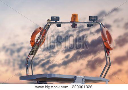 Nautical coast guard boat light and antena docked at marina with orange sky