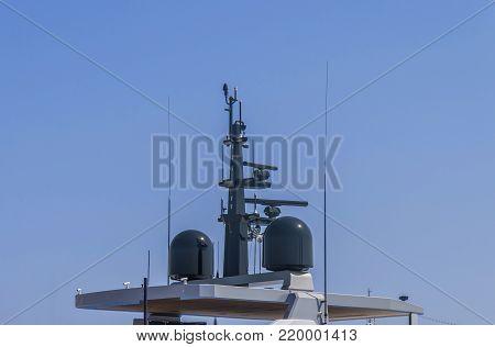 Nautical radio radar and antena at luxury yacht docked at marina