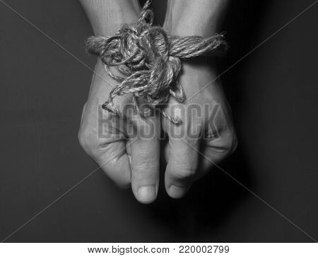 Male hands bound with rope on black