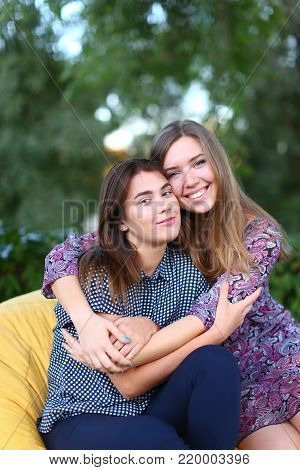 Portrait of two smiling lovely young women of European appearance posing for photo shoot or advertising of cosmetics or clothing catalogs. Women's successful students came to park after school to relax outdoors after hard day.