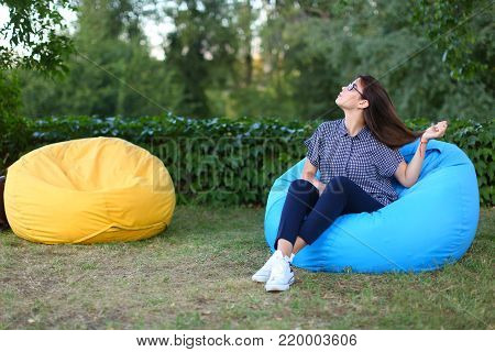 Good-looking girl resting from city bustle in blue soft and comfortable chair, straightens hairand poses for photo on background of green plants outdoors in park sunny day. Girl of European appearance with dark brown flowing hair with glasses
