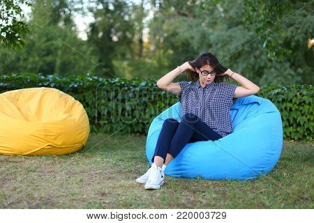 Good-looking girl resting from city bustle in blue soft and comfortable chair, straightens hairand poses for photo on background of green plants outdoors in park sunny day. Girl of European appearance with dark brown flowing hair with glasses dressed in