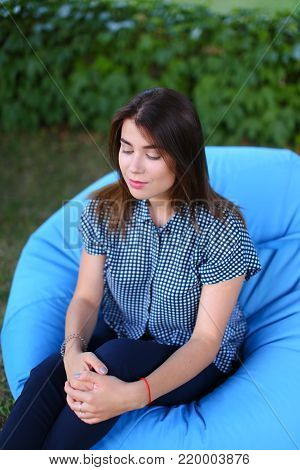 Shooting portrait of girl from above. Female resting from city bustle in blue soft and comfortable chair, poses for photo on background of green plants outdoors in park sunny day. Girl of European appearance with dark brown flowing hair dressed in blue pl