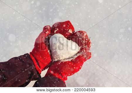 Snow heart in the gauntlets against snow background