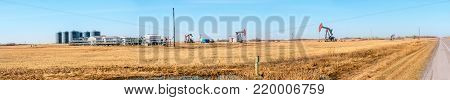 Oil Battery Gathering & Distribution System. Gas oil distribution station with cisterns and a compressor on a yellow field with pumps pumping oil