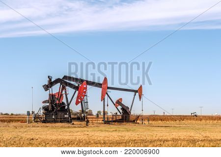On a summer, clear day, oil pumps pump oil on a yellow field. blue sky and white clouds in the background.