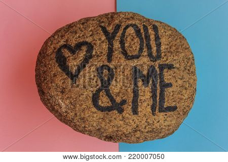 the english  writing you and me with a heart drawn on a stone  / the writing you and me with a heart drawn on a stone,indicates the love promise of two lovers