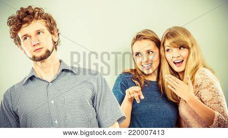Young women friends talking gossiping about man. Two women whispering sharing secret news.
