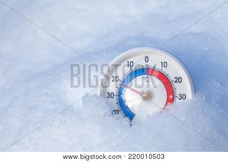 Thermometer with celsius scale placed in a fresh snow showing sub-zero temperature minus twenty two degree a cold winter weather concept