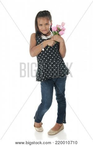 A pretty and bashful young mixed race elementary girl with a bouquet of pink roses.  On a white background.