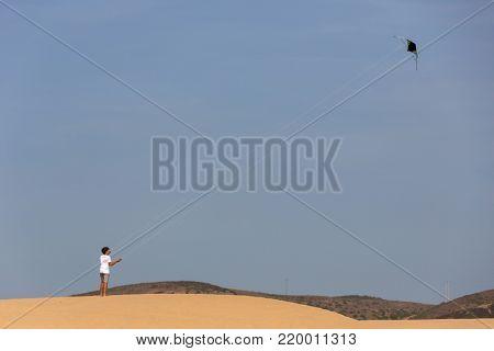 PRAIA DA BORDEIRA, PORTUGAL - AUGUST 20, 2017: young man playing with his kite at the dunes of the famous beach of Praia da Bordeira.