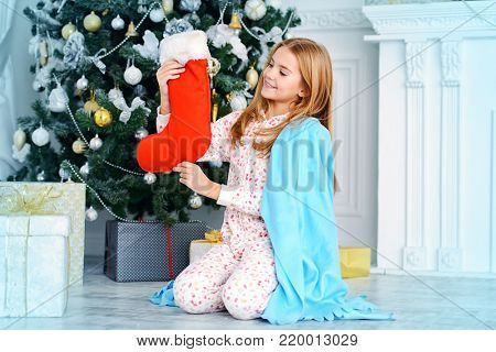 Pretty nine year old girl in pajama and covered with a blanket holding a christmas sock. Luxurious apartments decorated for Christmas. Merry Christmas and Happy New Year. Time for miracles.