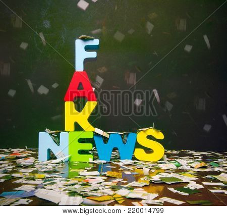 the word FAKE NEWS on a wooden floor with newspaper confetti
