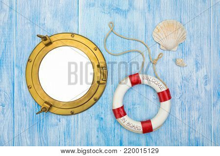 Maritime background, lifebuoy and sea shells on blue painted wood, brass porthole with copy space