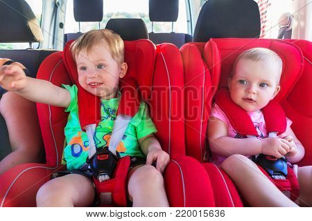 Little boy and girl twins seating in the car on child safety seats