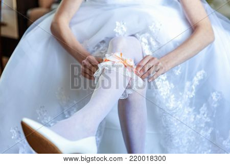 Garter on the leg of a bride, slim sexy bride in wedding luxury dress showing her silk garter. woman have a final preparation for wedding ceremony. Wedding day moments