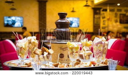 Chocolate fountain with fondue, fruits and sweets