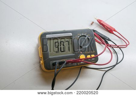 modern milliohmmeter with a connected resistor, lies on a white table.