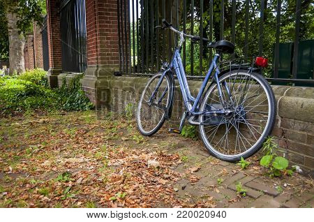 Bike leaned on the fence, autumn leaves on the ground.