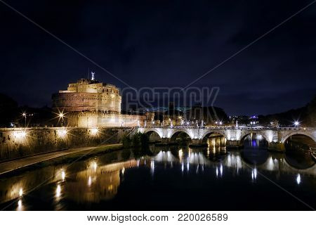 Night view of Castel Sant'angelo, mausoleum of Hadrian in Rome, Italy. In the scene is clearly visible the homonymous bridge in front, with its beautiful arches of white marble, under which flows the river Tiber.
