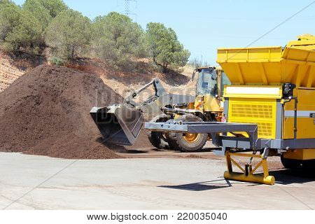 Industrial compost grinder fed by a bulldozer mulching garden waste into compost.