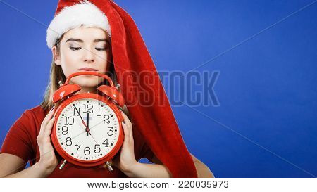 Xmas, seasonal clothing, christmas time concept. Worried woman wearing Santa Claus helper costume holding big red clock, waiting for celebration