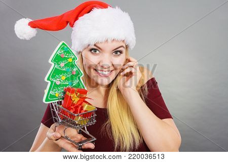 Xmas, seasonal sales, winter celebration concept. Happy woman wearing Santa Claus helper hat holding shopping basket cart with little christmas tree and gifts inside.