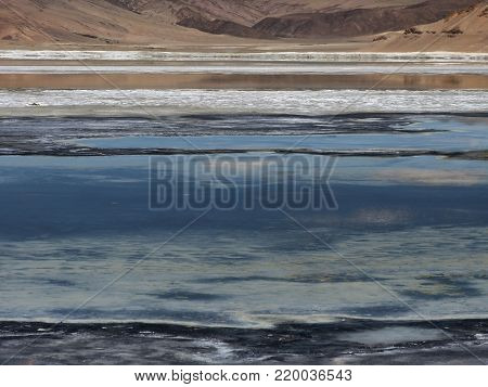 Abstract design background from different color stripes of blue lake, white rock salt and pink mountains.