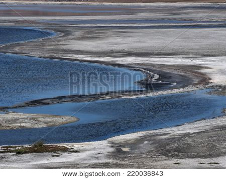 Abstract design background from blue stripes and semicircles of blue river water and white bands of saline.