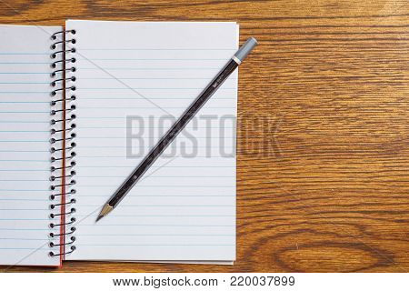 Top view of open spiral notebook with black pencil on desk background