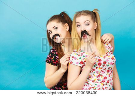 Two happy women holding fake moustache on stick having fun wearing tshirts with flower pattern. Photo and carnival funny accessories concept.