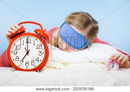 Sleeping young woman wearing cute pink pajamas holding big red old fashioned clock showing sleep time.